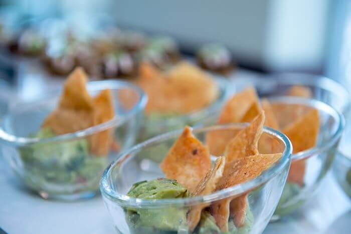 Martini glass of guacamole and homemade tortilla chips.